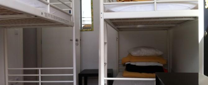 Dormitório Misto de 4 camas com casa de banho partilhada e varanda